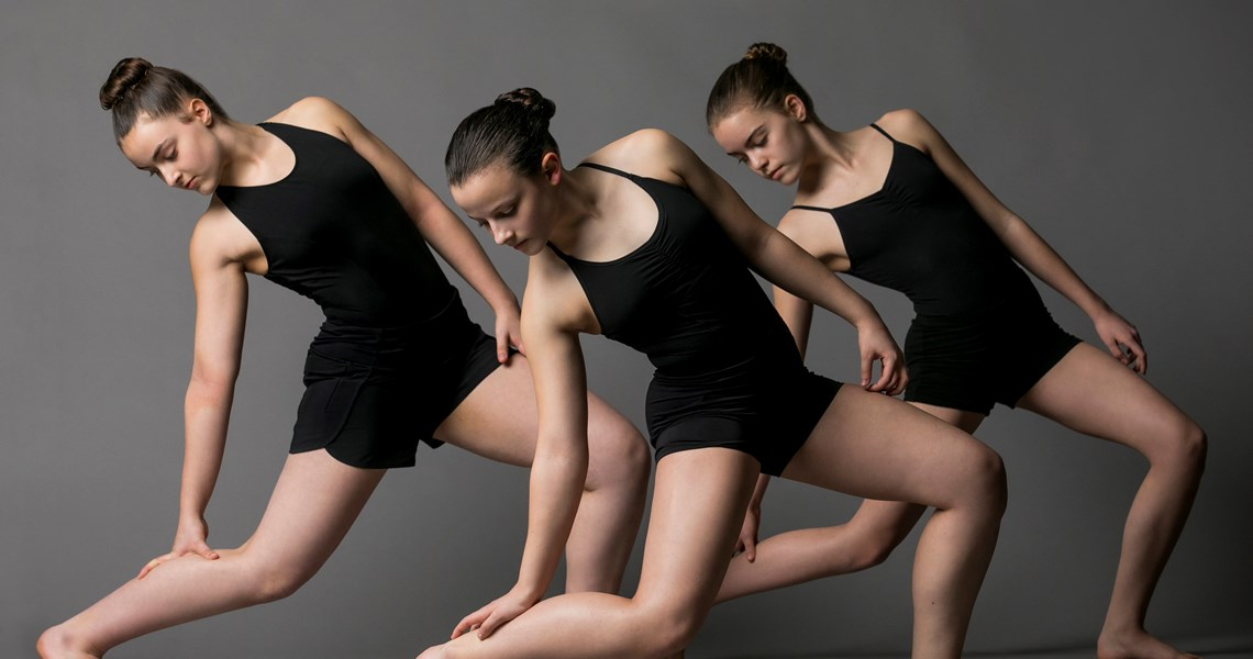 Three Youth Dance Program dancers leaning on their back legs