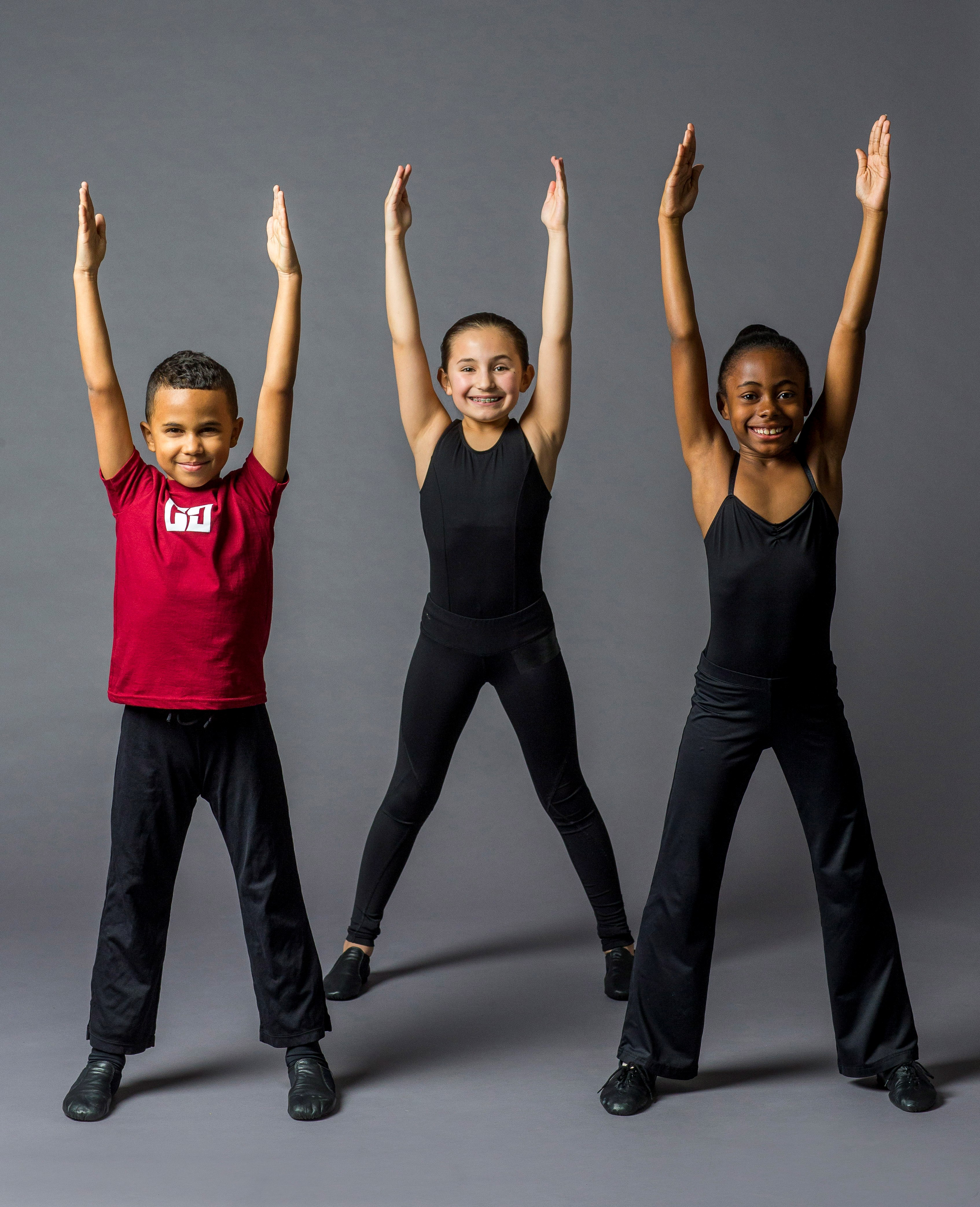 One boy and two girls in the Youth Dance Program stretching their arms above their heads.