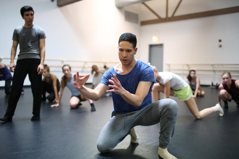 Young male dance student holding arms in front of him