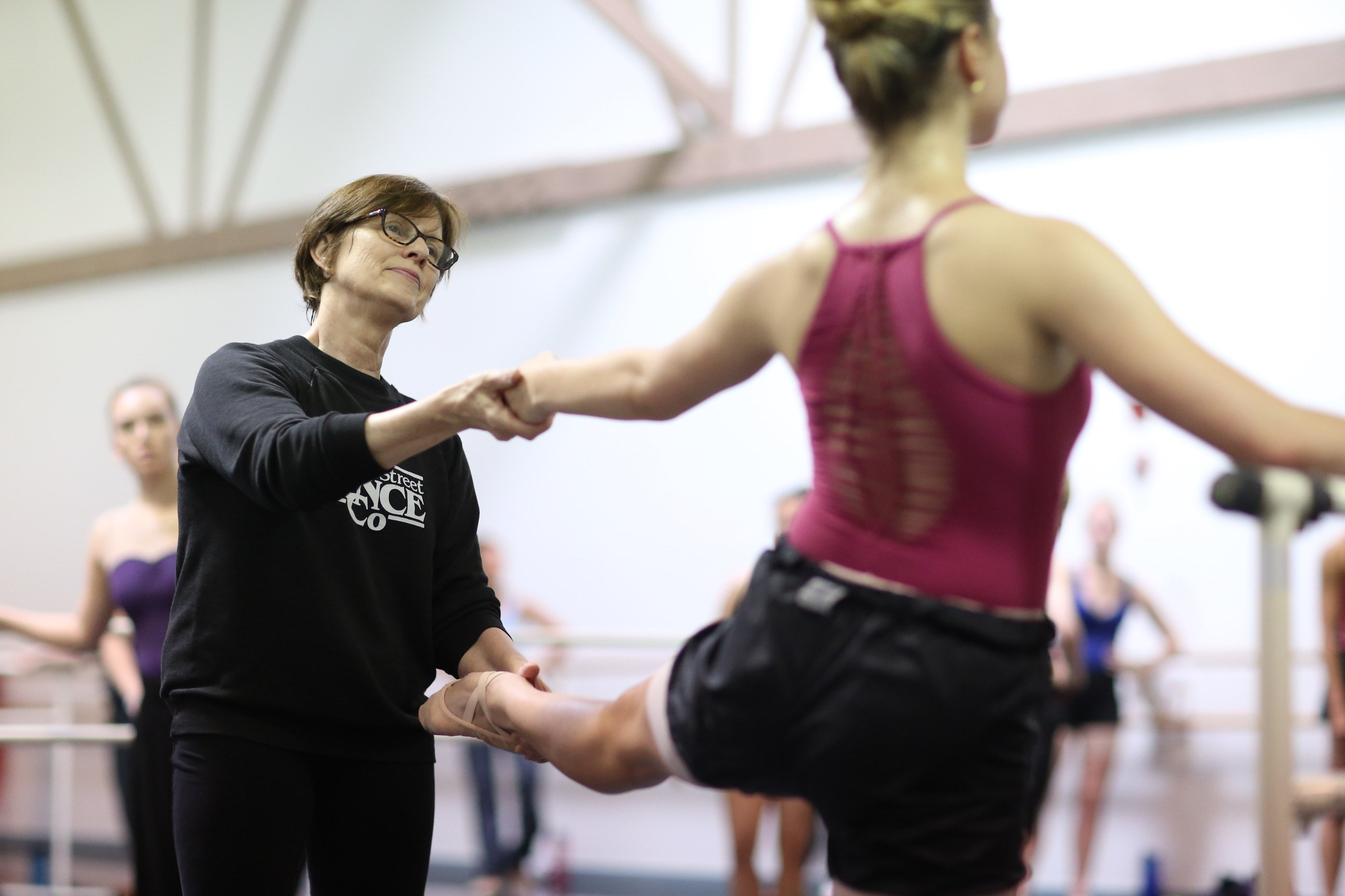 Lou Conte Dance Studio instructor Claire Bataille correcting a student's position in ballet