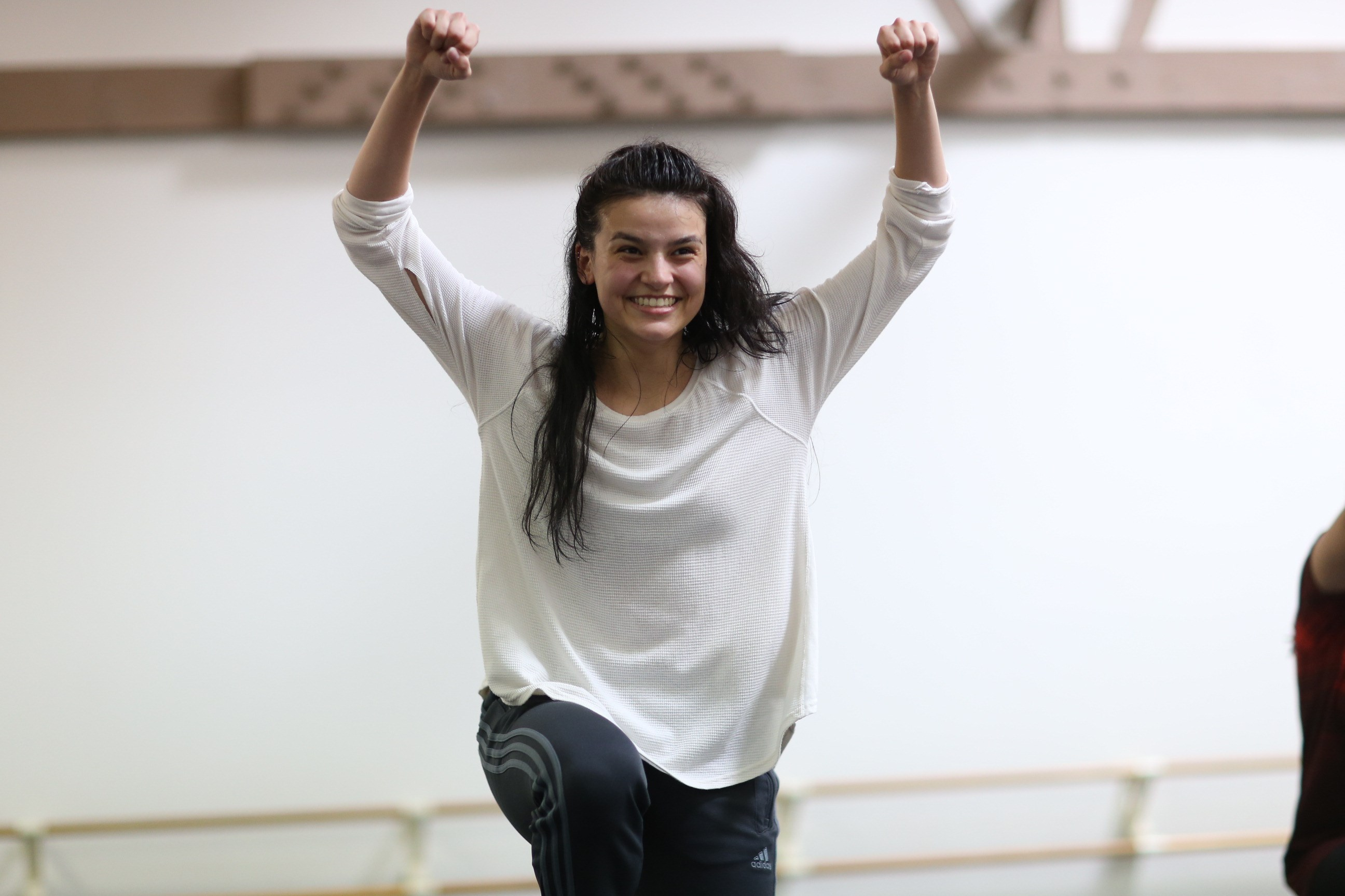 Young female dance student smiling with arms above her head