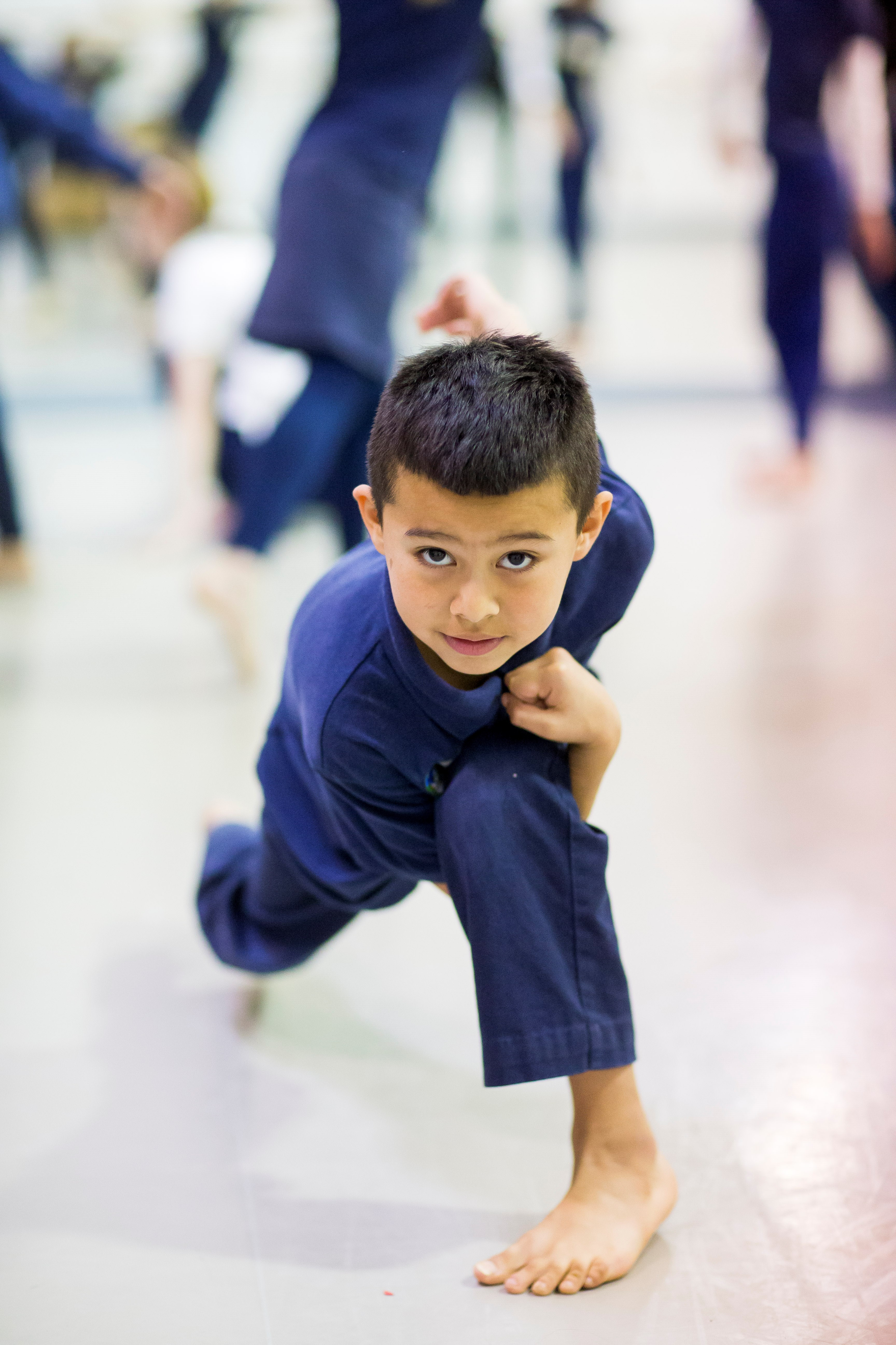 Young boy crouches down and strikes a pose during an in-school dance residency