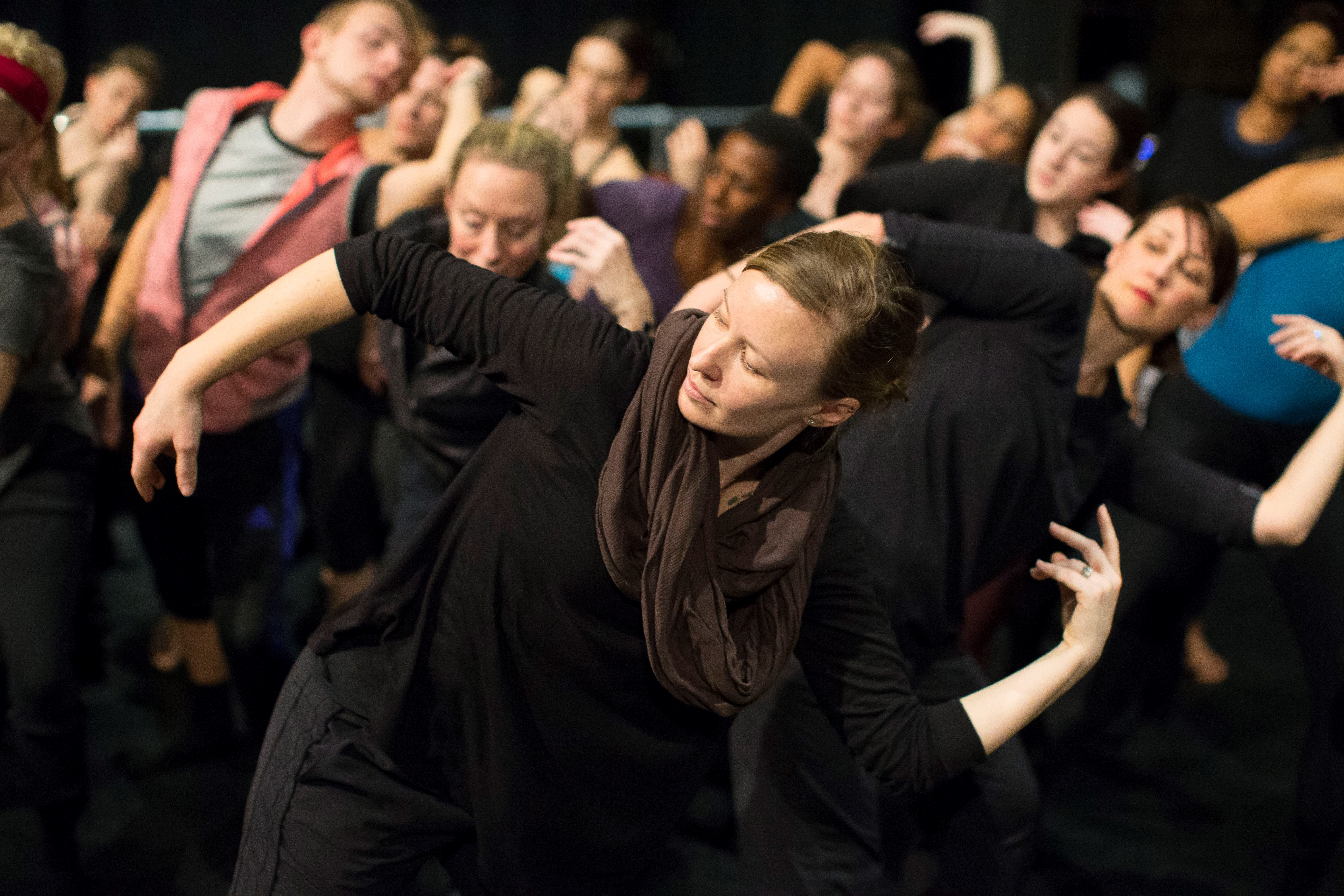 Woman in brown scarf leads class through dance techniques