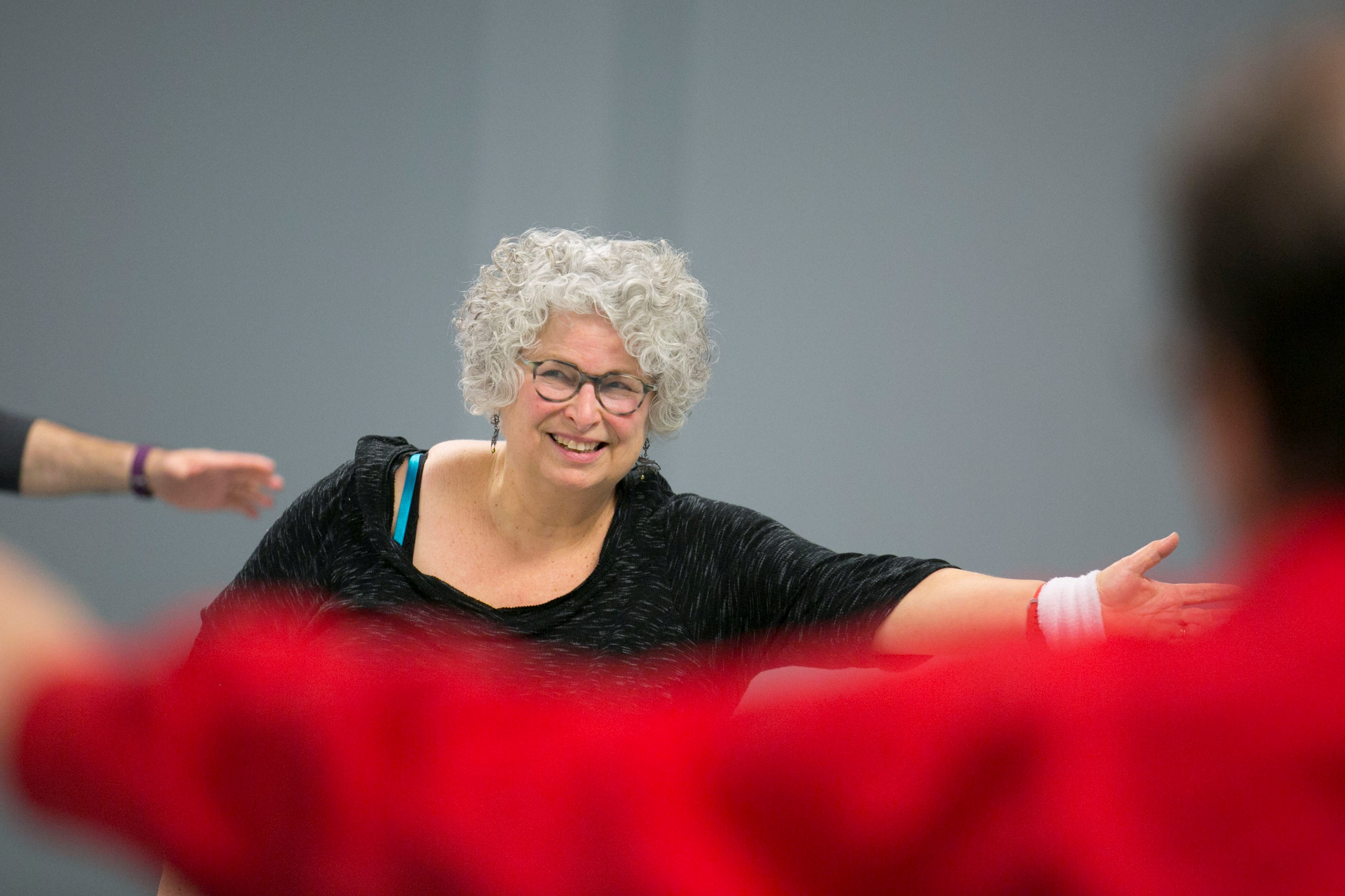 Older woman stretches out her left arm in dance class