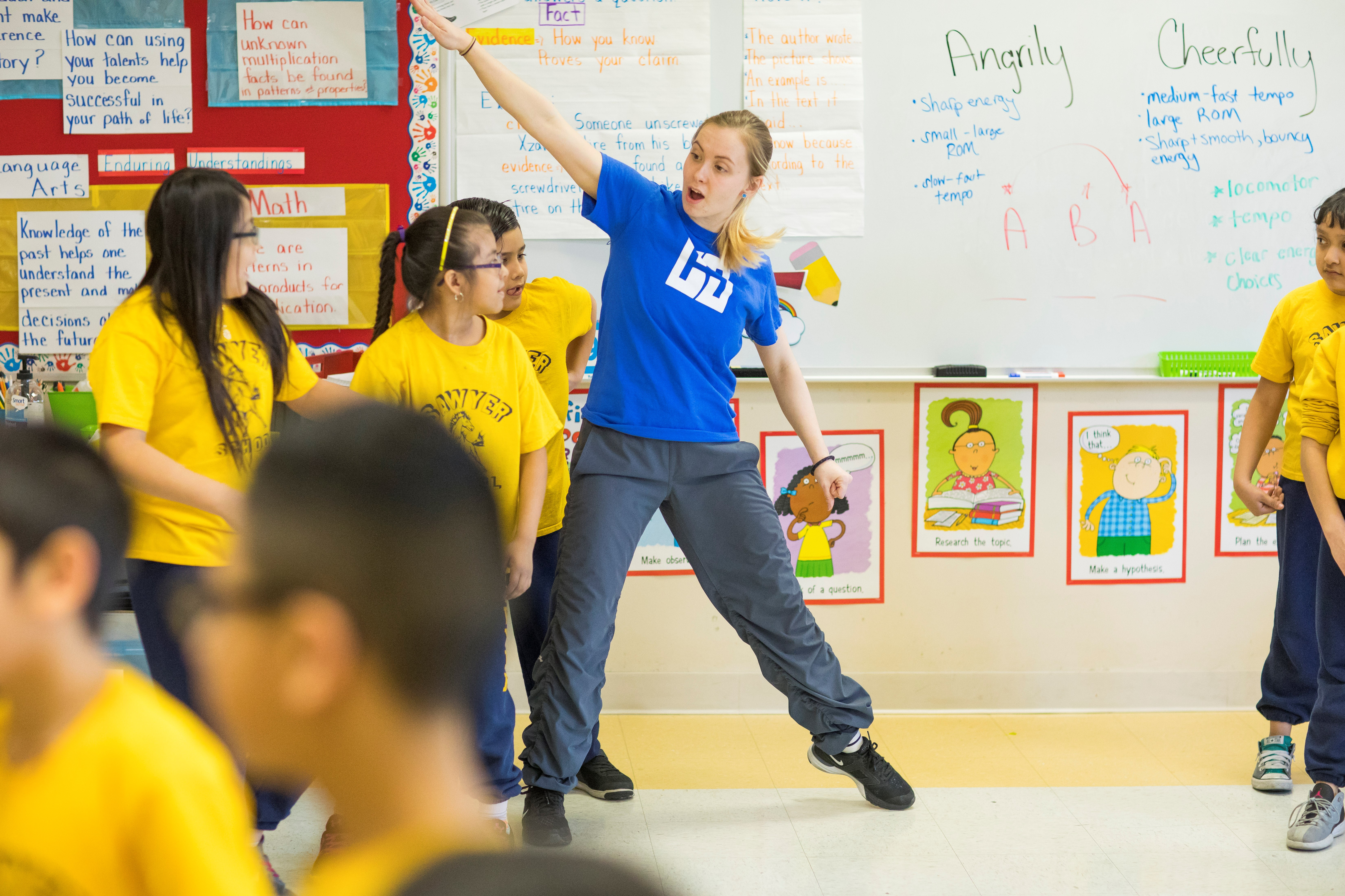 Young woman leads elementary school students through a dance warm up
