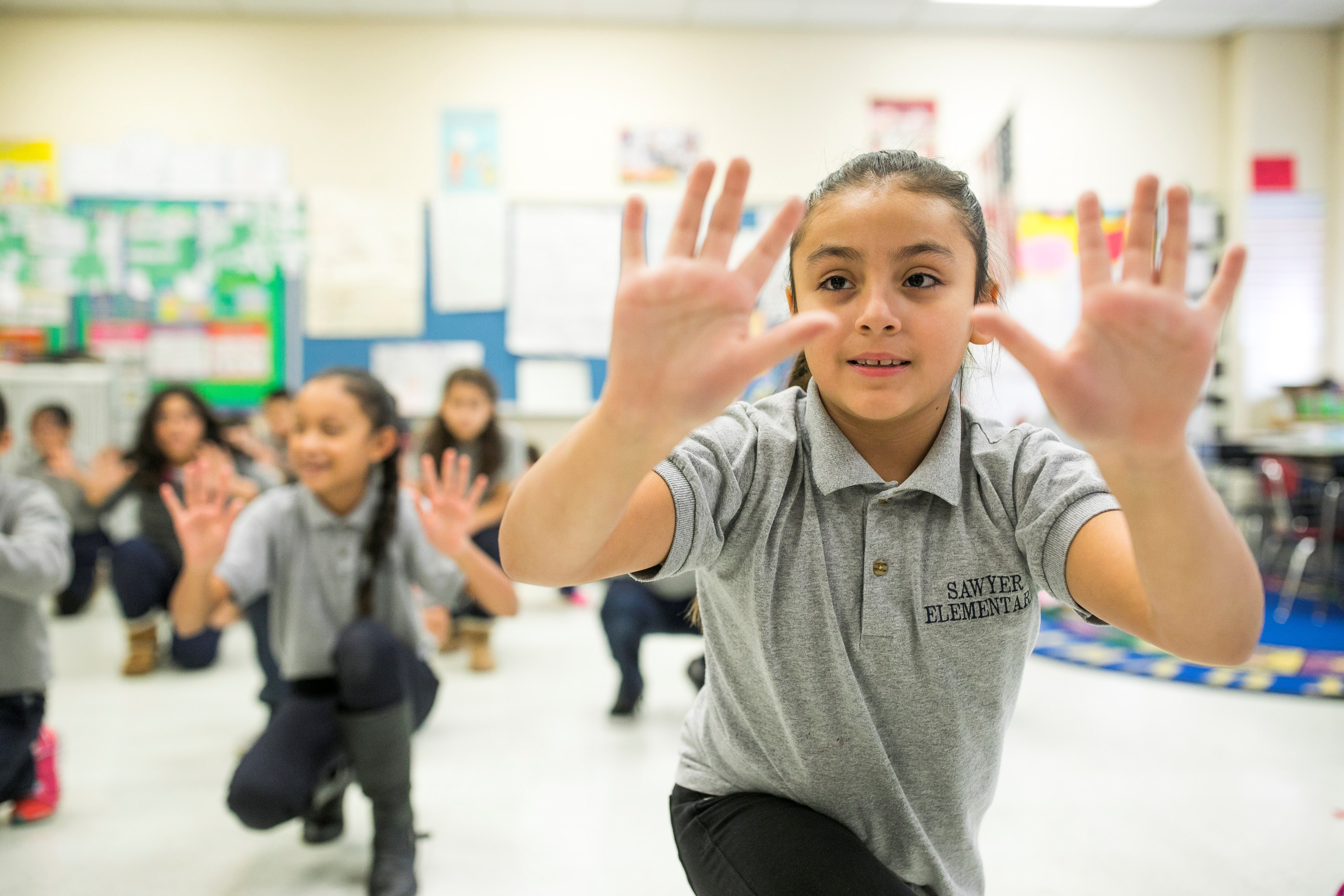Young girl holder her hands out in front of her face during an in-school dance residency