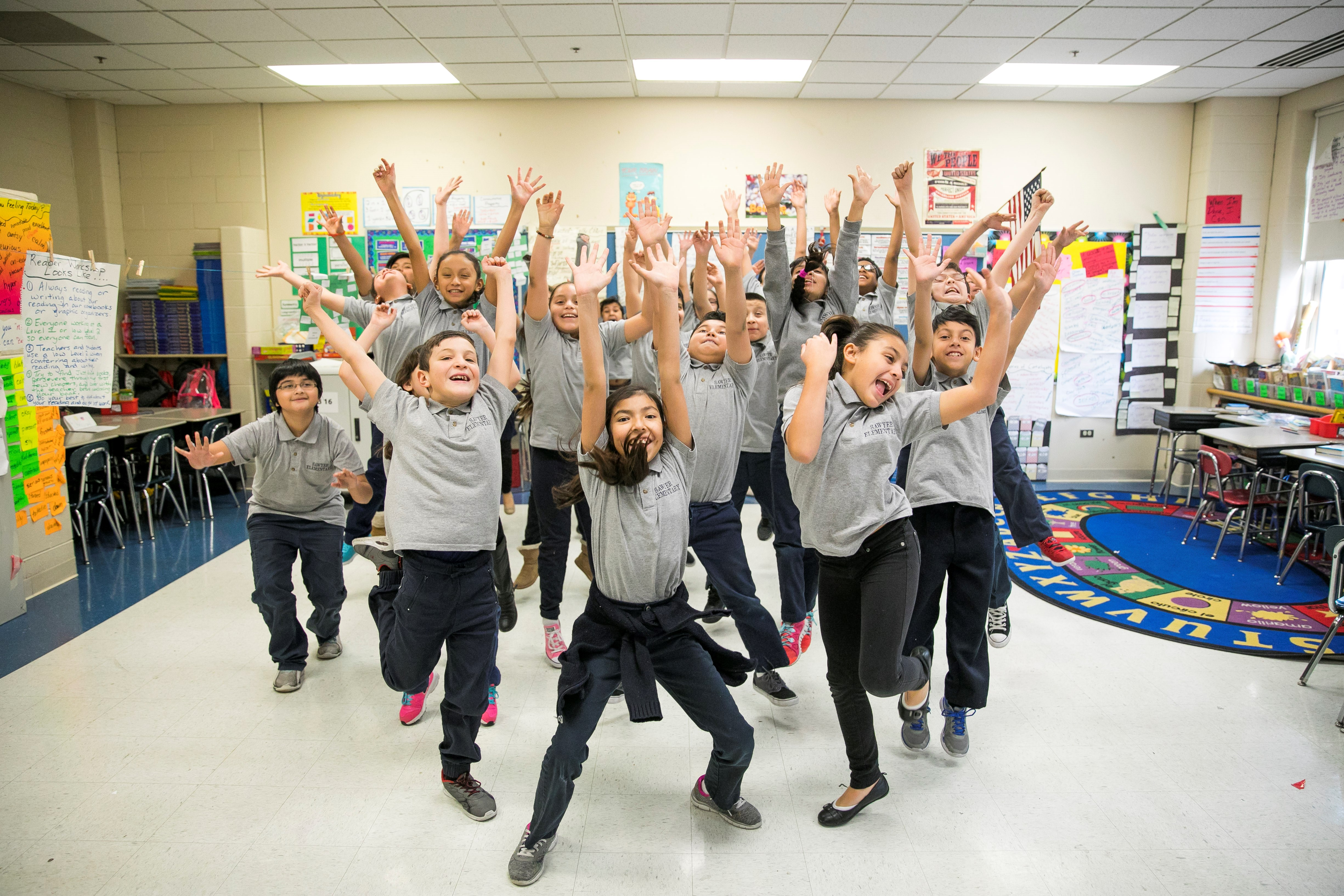 Students jump with their hands above their heads during an in-school dance residency